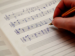 hand writing music with pen on sheet paper
